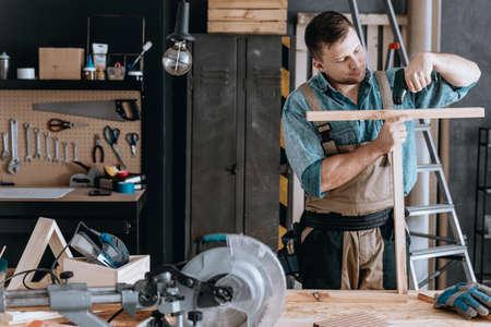 Man die twee stukken hout samenvoegt terwijl hij meubels maakt