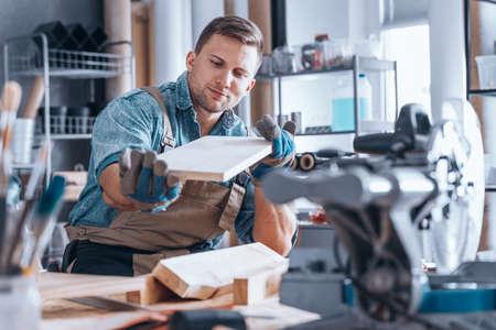 Mannelijke timmerman die een stuk hout na het schuren in zijn workshop onderzoeken