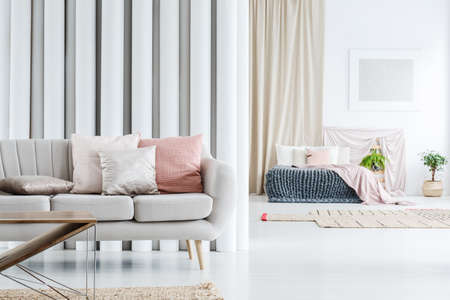 Silver and pastel pink pillows placed on bright couch in stylish living room with bedroom in the background Stock Photo