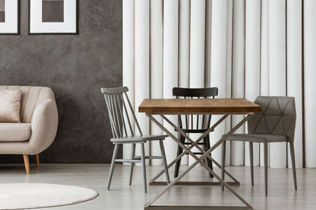 Grey chairs at designer table against paper tubes wall in interior with carpet and sofa