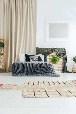 Silver modern painting hanging on white wall above bedhead with plant in cozy bedroom