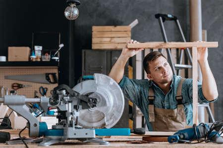 Timmerman die een meubel in een workshop met cirkelzaag en boor maakt Stockfoto