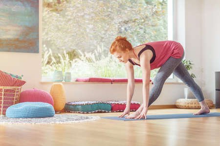 Sportswoman in sportswear stretching on a mat near the window, at home Stock Photo