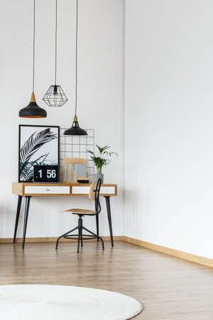 Simple desk and wooden chair standing in the corner of modern office interior