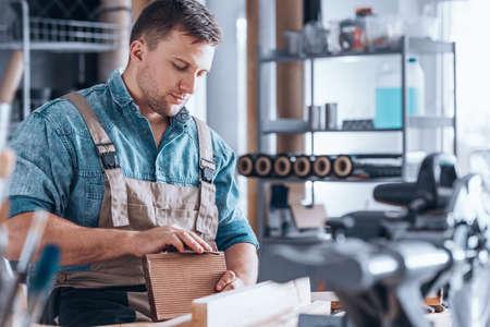 Jonge, geconcentreerde arbeider die het overhemdszitting van Jean dragen bij zijn bureau in een reparatiewerkplaats