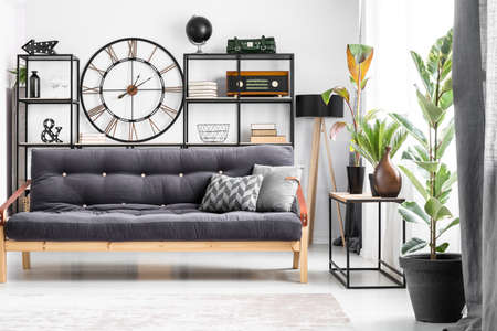 Black wood and leather couch with a patterned cushion standing in bright living room interior with clock on the wall
