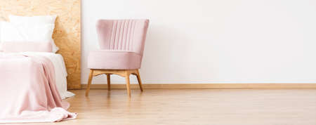 Pink chair next to bed with wooden bedhead against white wall with copy space in cozy bedroom