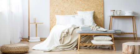 Pouf and wood in warm natural bedroom with white pillows on bed and bench near table with candles