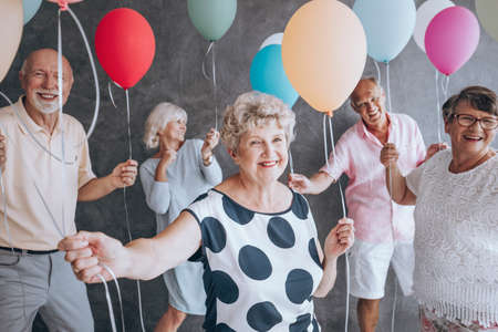 Smiling grandmother wearing a blouse with black dots during New Years Eve party with friends holding colorful balloons