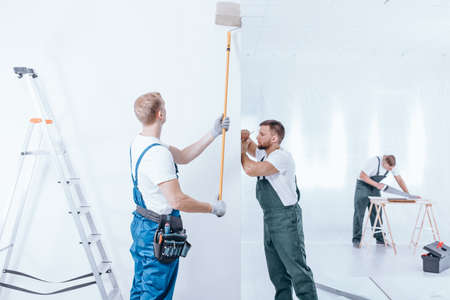 Home renovation crew in overalls finishing white interior using different equipment