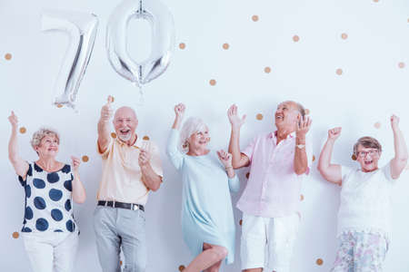 Positive seniors family celebrating grandfathers birthday with silver balloons