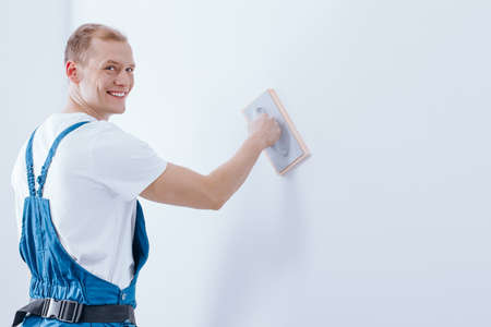 Smiling handyman in blue overalls priming the substrate of white wall