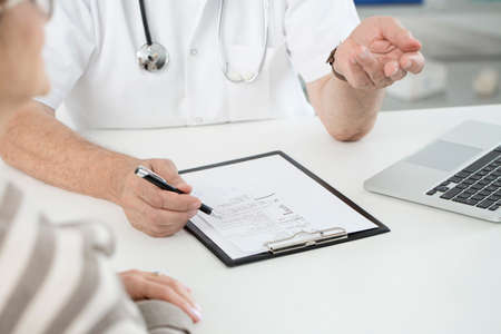 Close-up of general doctor writing a prescription using black pen during patient examination