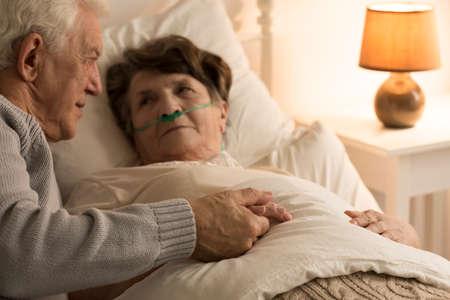 Bejaarde ondersteunend zijn zieke vrouw die in bed thuis ligt