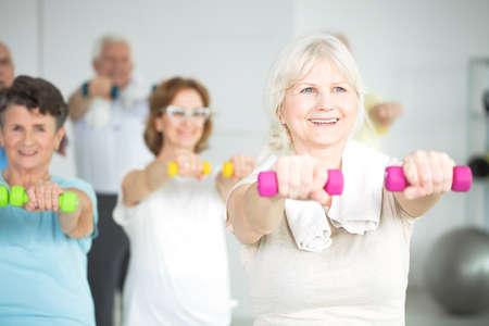 高齢者のためのグループエクササイズクラス中にダンベルを持つ高齢女性