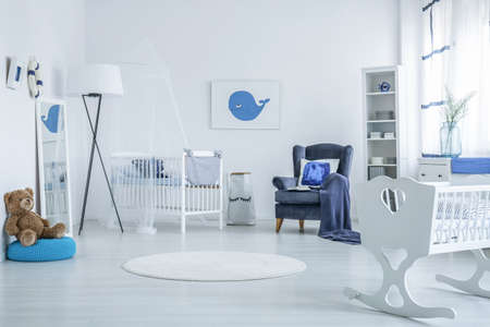Teddy bear on blue pouf and white cradle in bright kids bedroom with lamp, carpet and armchair