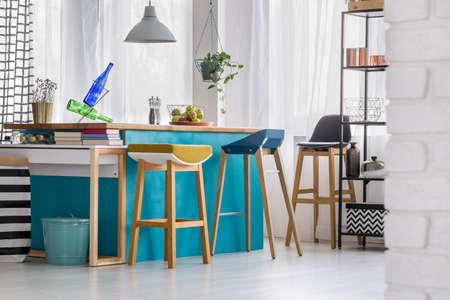 Designer bar stools at blue kitchen island with bottles under grey lamp in bright kitchen interior with bin