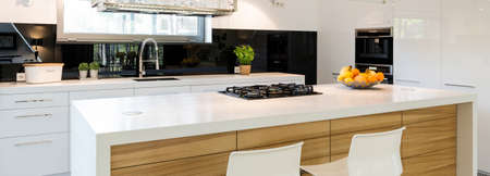 Black, white and wood in modern fitted kitchen Stock fotó