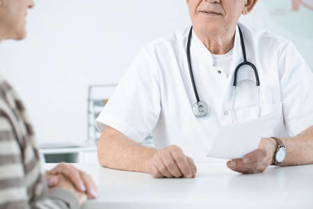 Close-up of doctor with stethoscope giving prescription to a weak patient