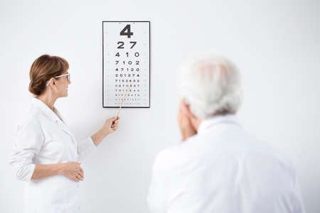 Ophthalmologist indicating letters on the board during examining a patient Reklamní fotografie