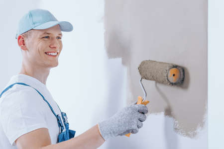 Happy painter wearing a hat and gloves painting the wall beige using roller