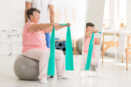 Elderly woman sitting on grey ball in front of mirror and exercising shoulders muscles with resistance band