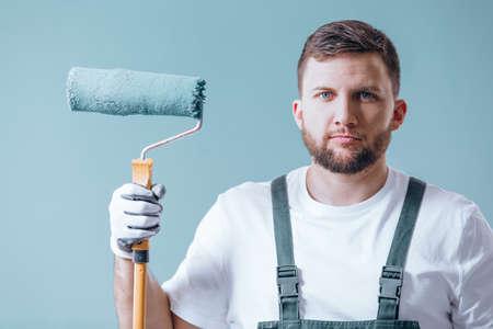 Professionele schilder met blauwe roller na het schilderen van een muur met blauwe verf Stockfoto
