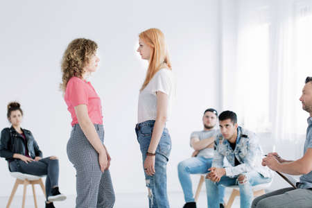 Young girls facing each other during psychotherapy with rebellious teenagers in white office