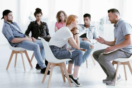 그룹 치료 중 젊은 반항적 인 소녀와 이야기하는 카운슬러