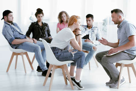 Counselor talking with young rebellious girl during group therapy Zdjęcie Seryjne - 93360913