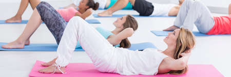 Participant of fitness classes  are lying on mats and raise torsos to stretch the muscles of the abdomen Banco de Imagens