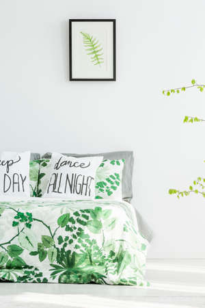 Drawing of fern leaf in a black frame hanging on white wall in room interior with floral bed