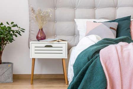Nahaufnahme des dunklen Vase mit Blumen auf weißem Nachttisch nahe bei Bett mit den rosa und grünen Bettlaken im Pastellschlafzimmerinnenraum Standard-Bild - 93732049