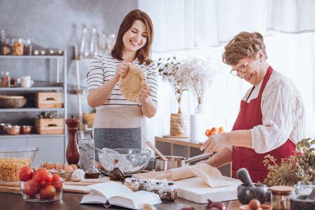 Jong vrouw het kneden deeg tijdens het koken met grootmoeder