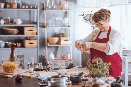 Grootmoeder die ei toevoegt aan bloem terwijl het koken in de keuken