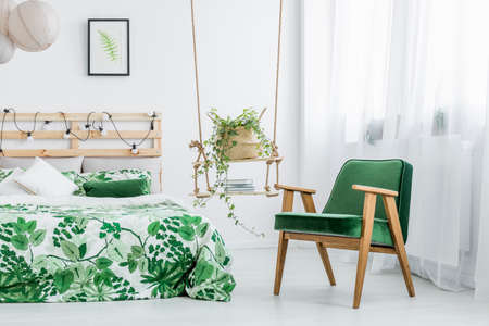 Fresh plant in wicker basket and books placed on diy hanging shelves in floral bedroom interior with armchair