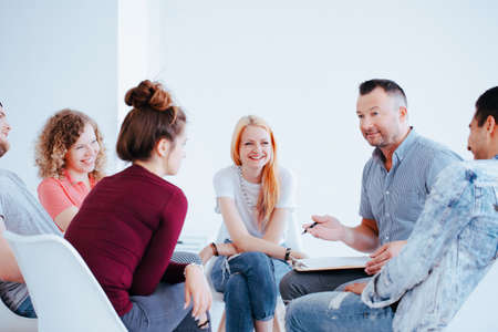 Smiling group of teenagers during a meeting with personality coach helping them to gain self-confidence Stock Photo