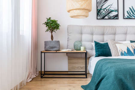 Plant, vase and book on table next to bed with beige bedhead and green bedding in cozy bedroom interior with floral posters