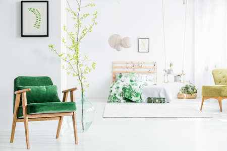 Fresh twig with leaves in big glass vase standing next to a green velvet armchair in bright bedroom interior