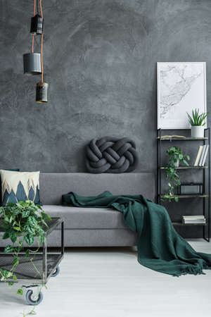 Dark green blanket on grey sofa against concrete wall in guy room interior with designer lamp and map poster on the wall