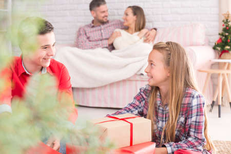 Young and happy family unpacking gifts in christmas morning Imagens