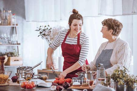 Vrouwen in keukenschorten die samen op countertop met ingrediënten in de keuken koken