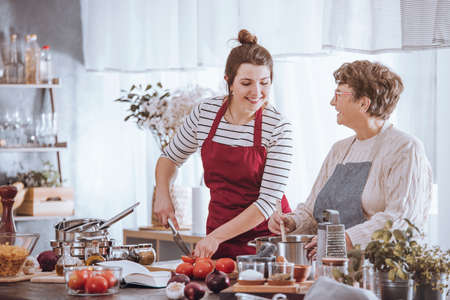 Women in kitchen aprons cooking together on countertop with ingredients in the kitchen Stockfoto