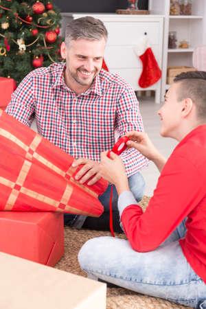 クリスマスの時期に幸せな父と息子の梱包プレゼント 写真素材