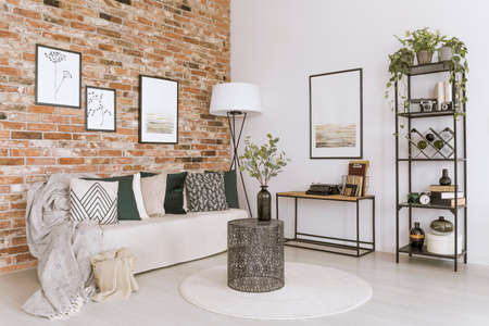 Beige blanket and pillows on a settee against brick wall in living room with vase on metal table
