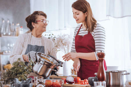Grandma and granddaughter cooking tomato soup in the kitchen Stock Photo