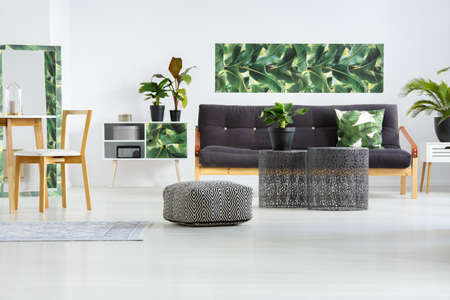 Pouf next to metal tables in front of a black settee against white wall with green leaves poster in floral living room interior with wooden chair