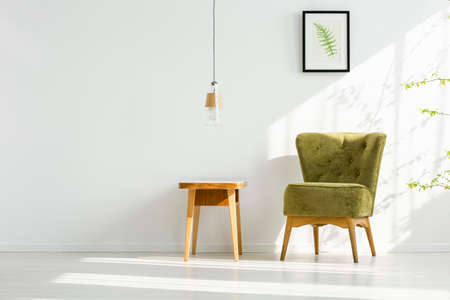 Small wooden table and green armchair standing in a simple room interior with lamp and fern poster