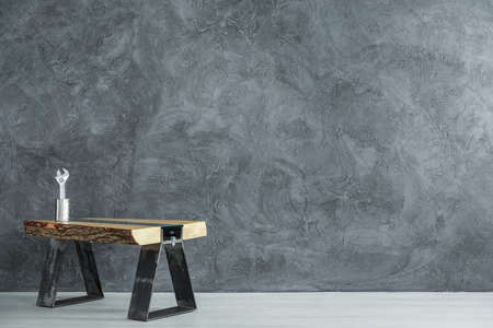 Work table with tool in metal can against concrete wall in handymans empty dark room, copy space interior concept