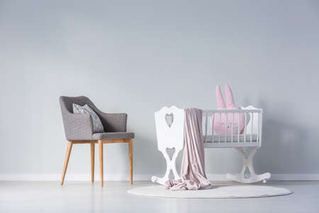 Pink pillow and blanket in white cradle next to a grey chair in simple babys bedroom interior with copy space